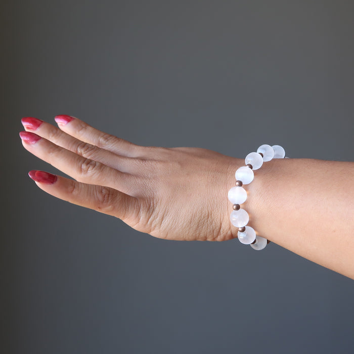 hand wearing white selenite and antique beads stretch bracelet