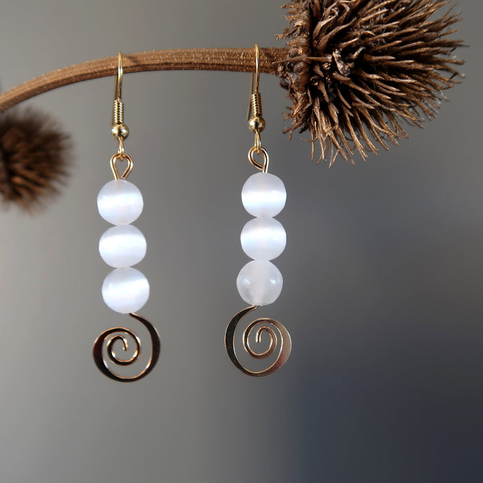 white selenite gold spiral dangle earrings hanging off a branch