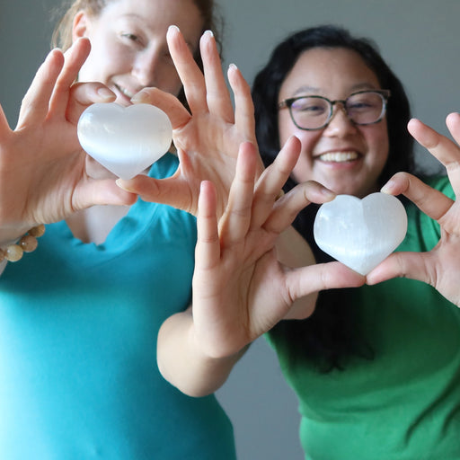 jamie and jessica of satin crystals holding white selenite hearts