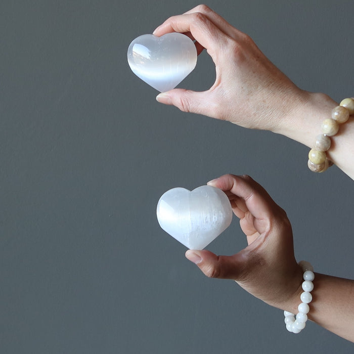 two hands each holding a selenite heart