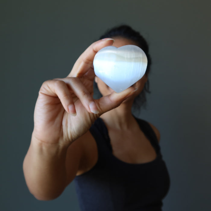 sheila of satin crystals holding a white selenite heart in front of her face