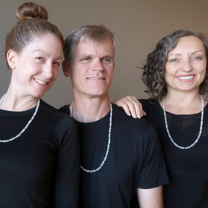 two women and one man wearing white selenite necklaces