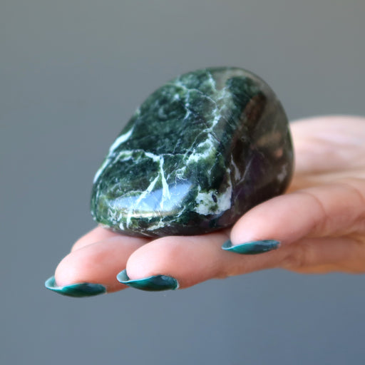 hand holding dark green and white serpentine polished stone