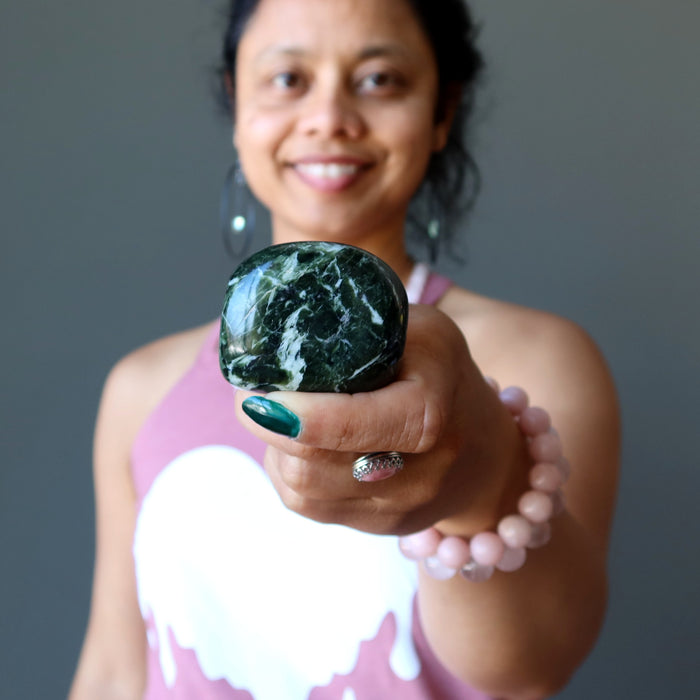 sheila of satin crystals holding dark green and white serpentine polished stone