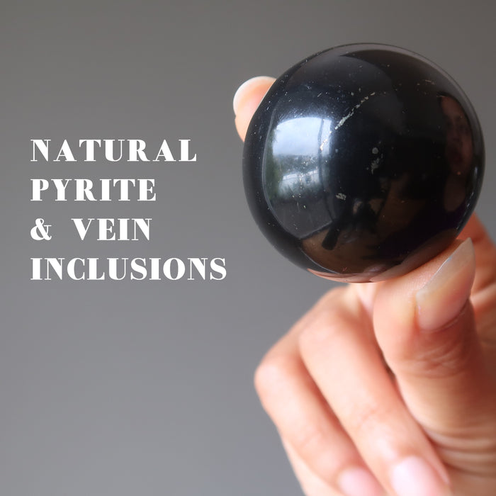 hand holding a shungite crystal sphere showing natural pyrite and vein inclusions