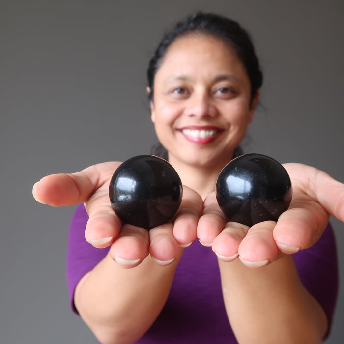 sheila of satin crystals holding two shungite spheres in her hands