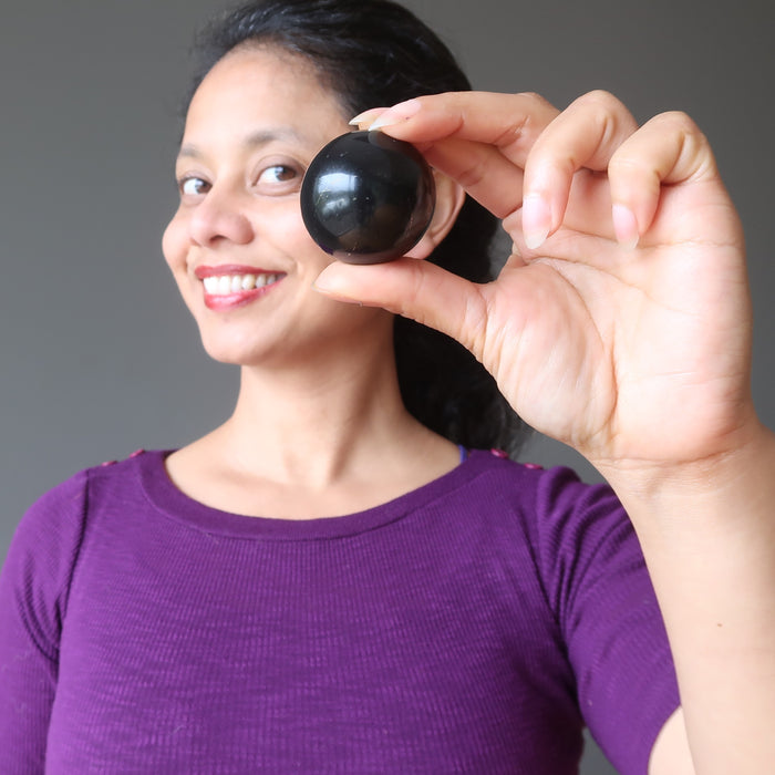 sheila of satin crystals holding up a shungite sphere