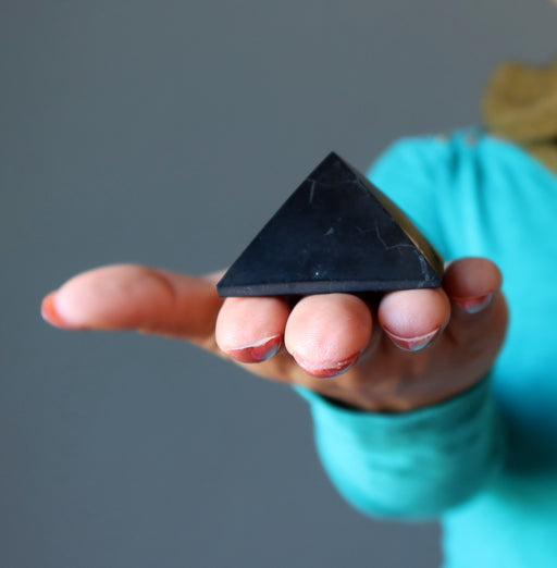 hand holding black shungite stone pyramid showing natural mineral inclusions