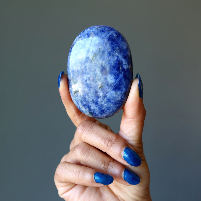 hand holding up a blue and white sodalite oval polished stone slab