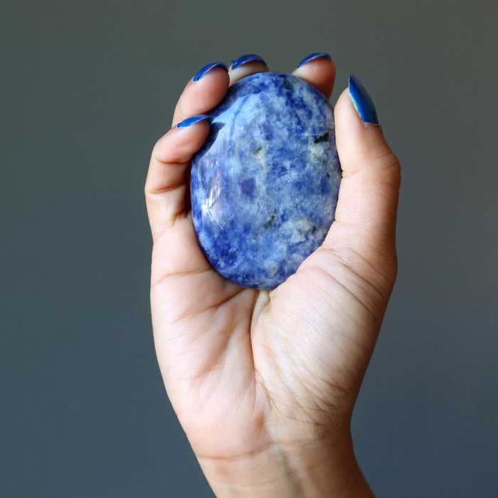 blue and white sodalite oval polished stone slab in palm of hand