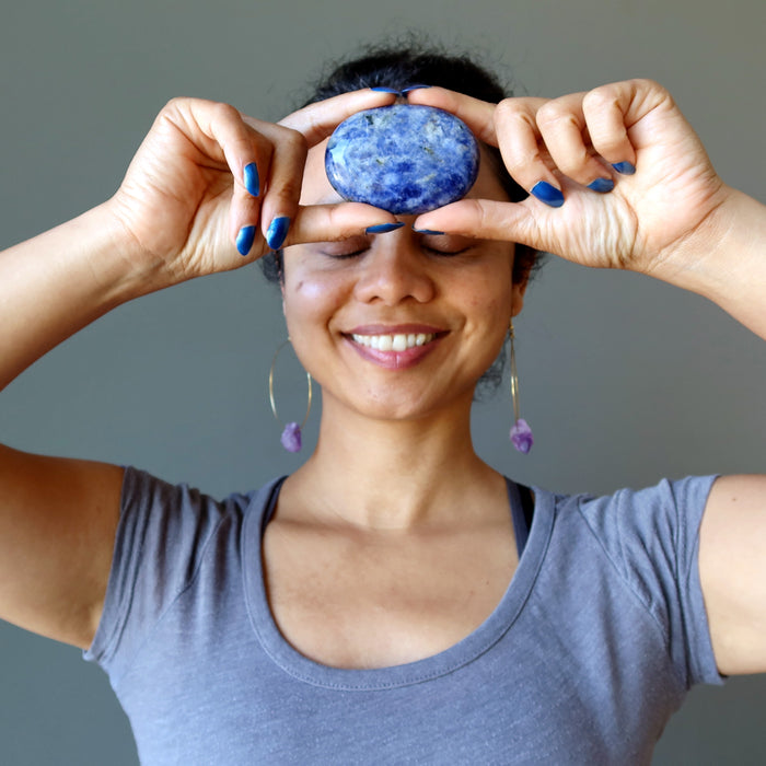 sheila of satin crystls holding blue and white sodalite oval polished stone slab at third eye chakra