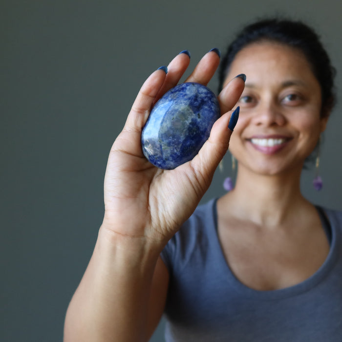 sheila of satin crystals holding blue and white sodalite oval polished stone slab in palm of hand