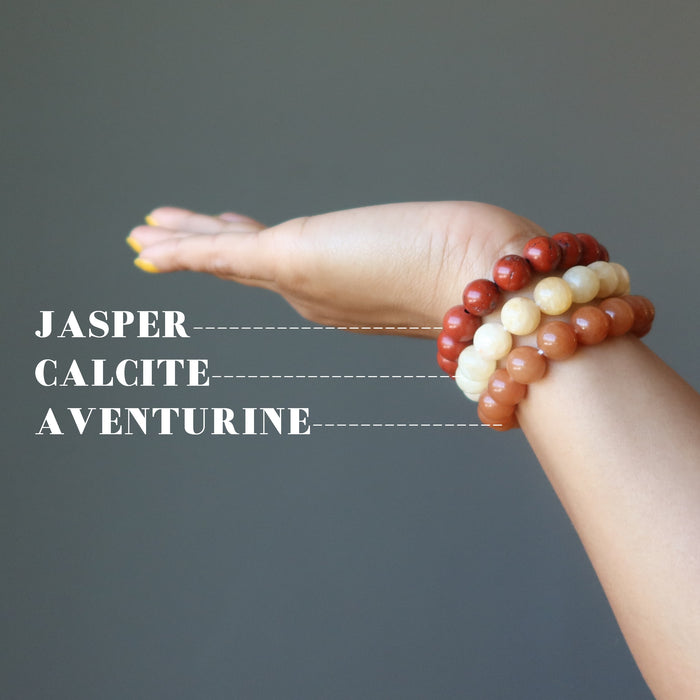 hand wearing yellow calcite, orange aventurine, red jasper stretch bracelet set