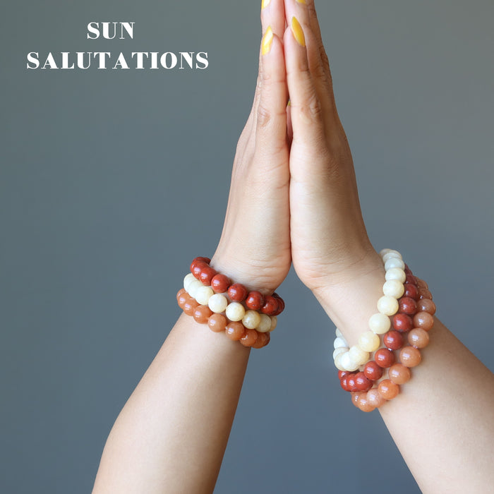 hands in prayer for sun salutation wearing yellow calcite, orange aventurine, red jasper stretch bracelet sets