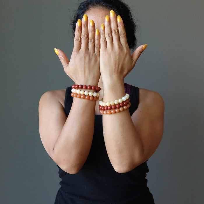 sheila of satin crystals wearing yellow calcite, orange aventurine, red jasper stretch bracelet sets on both wrists with hands covering face