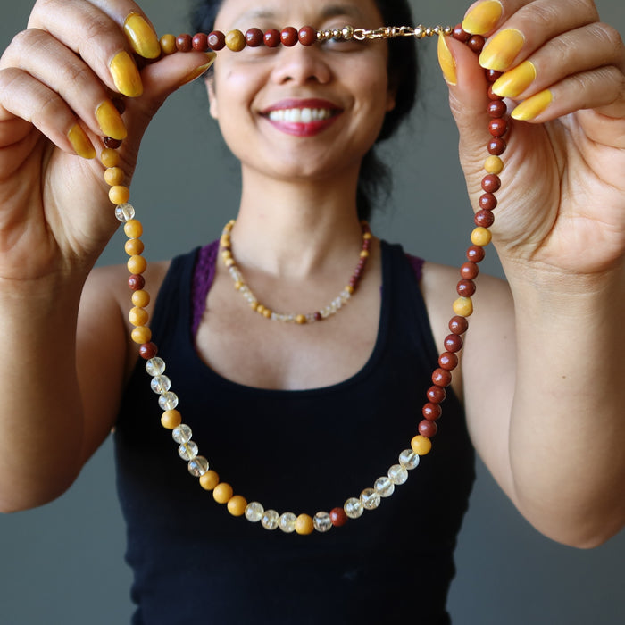 sheila of satin crystals holding up a red jasper, yellow jasper and citrine beaded necklace