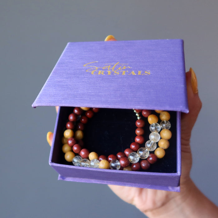 hand holding a satin crystals gift box with red jasper, yellow jasper and citrine beaded necklace