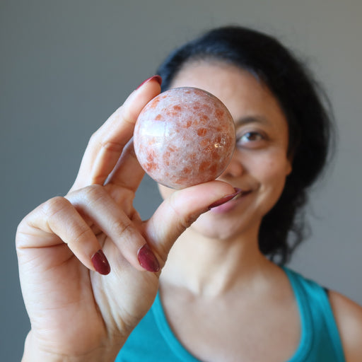 sheila of satin crystals holding up a sunstone sphere
