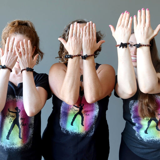 three females wearing tektite obsidian bracelets and satin crystals shirts