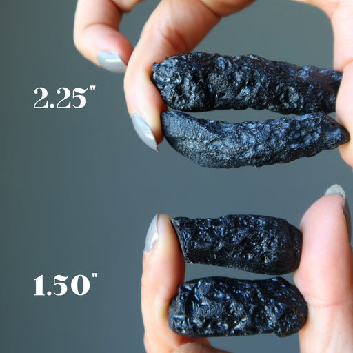 hands holding two sets of rough black tektites to show size difference