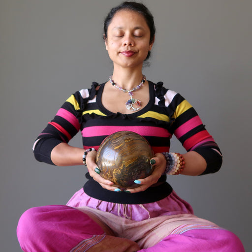 sheila of satin crystals meditating with a giant brown tigers eye sphere with veins of black hematite