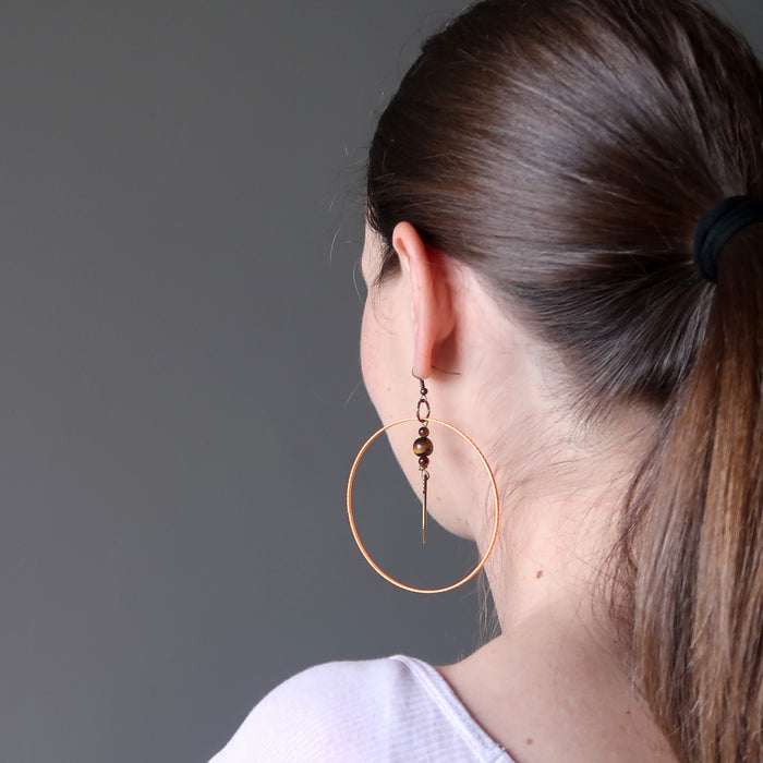 lucia of satin crystals wearing tigers eye arrow orange hoop earrings