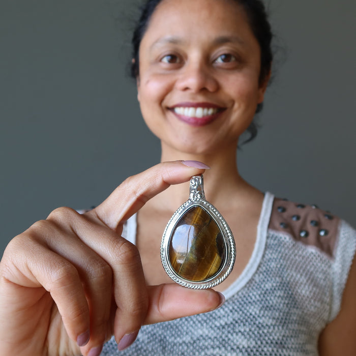 sheila of satin crystals holding golden brown tigers eye teardrop in silver pendant