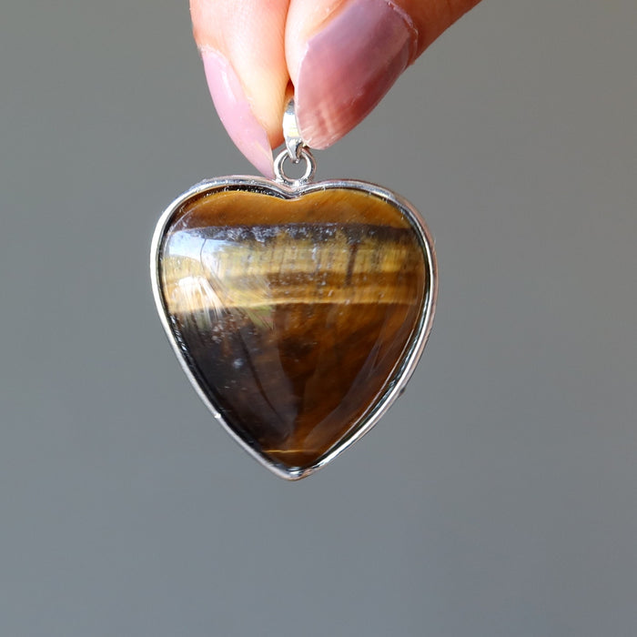 fingers holding golden brown tigers eye heart in silver frame pendant