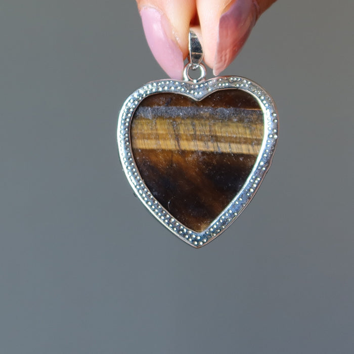fingers holding golden brown tigers eye heart in silver frame pendant showing the backside