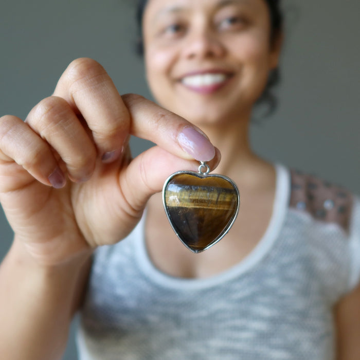 sheila of satin crystals holding golden brown tigers eye heart in silver frame pendant