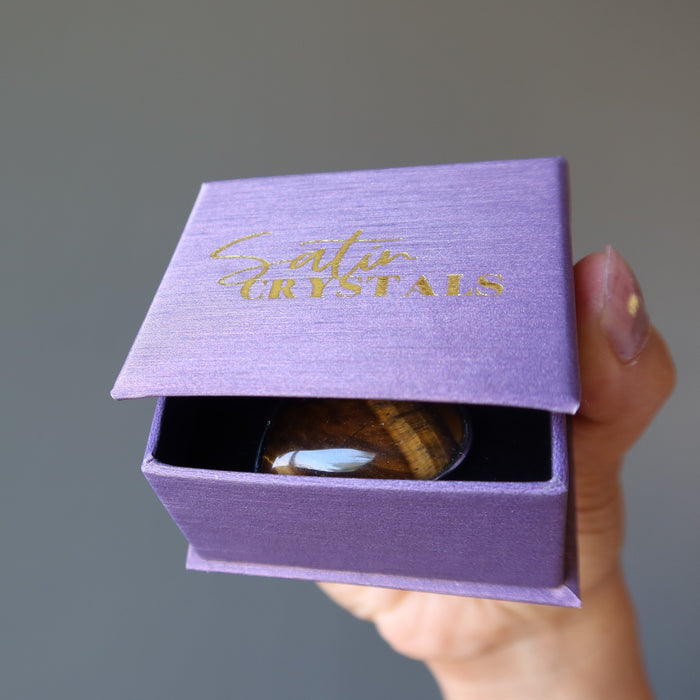 holding golden brown tigers eye heart in silver frame pendant in a purple satin crystals gift box