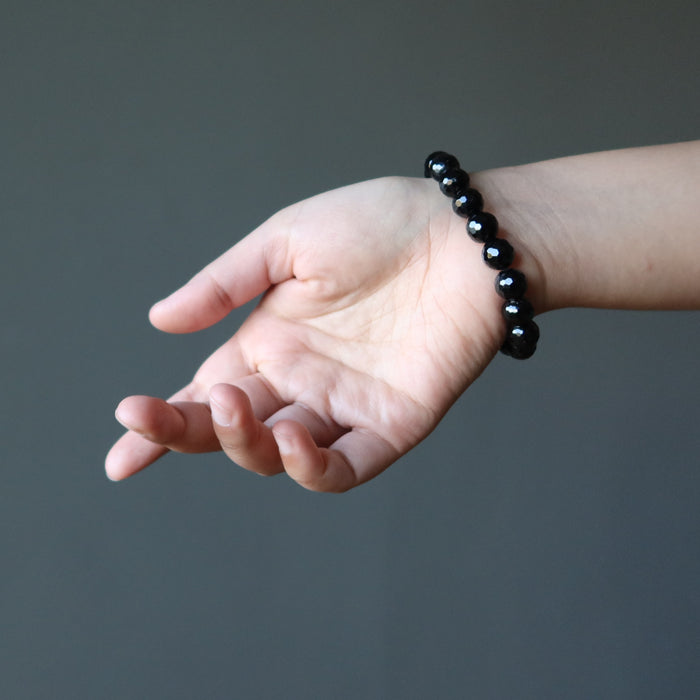 hand wearing a faceted black tourmaline stretch bracelet