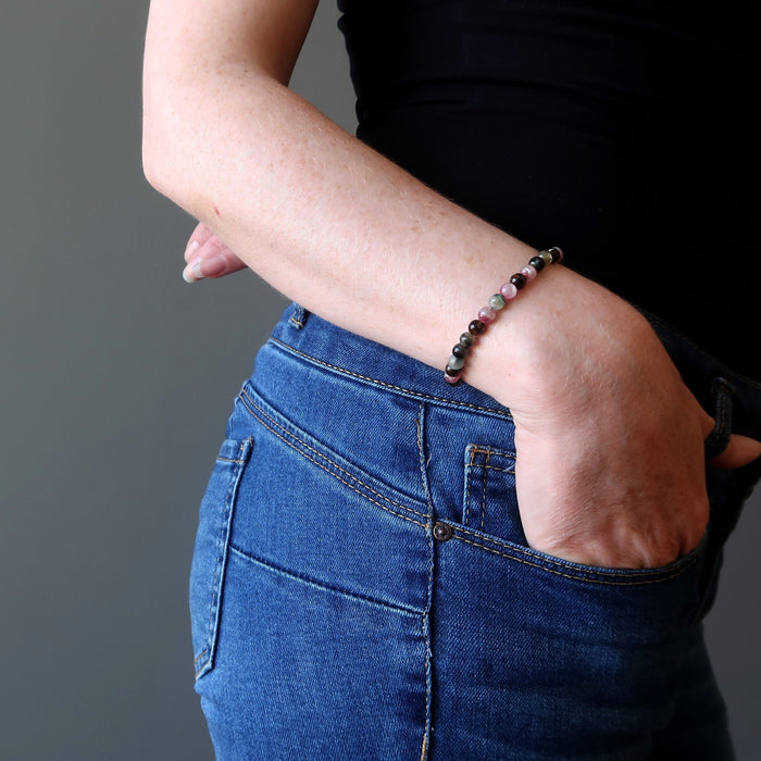 female model with hand in jeans pocket wearing a rainbow tourmaline bracelet