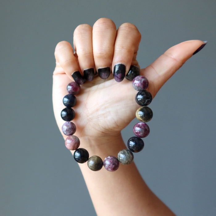hand holding multi colored tourmaline stretch bracelet