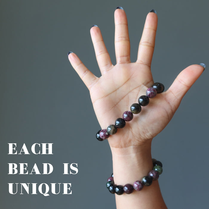 hand wearing two multi colored tourmaline stretch bracelets to show varying colors
