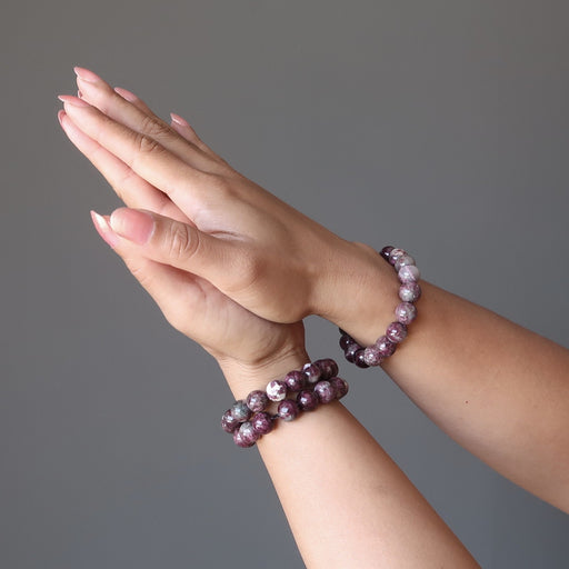 pair of hands in prayer pose wearing 3 Pink Tourmaline bracelets with lush raspberry tones in round smooth beads