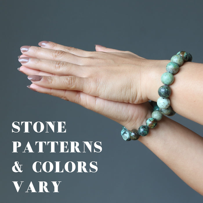 hands clasped wearing african turquoise bracelets to show stone patterns and colors vary
