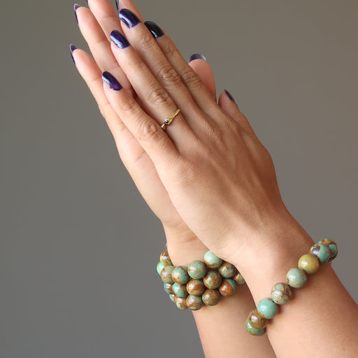hands clasped wearing 4 green and brown turquoise jasper round beaded stretch bracelet