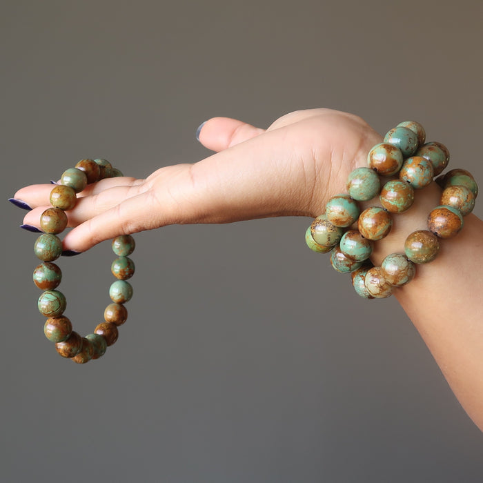 hand wearing and holding green and brown turquoise jasper round beaded stretch bracelets
