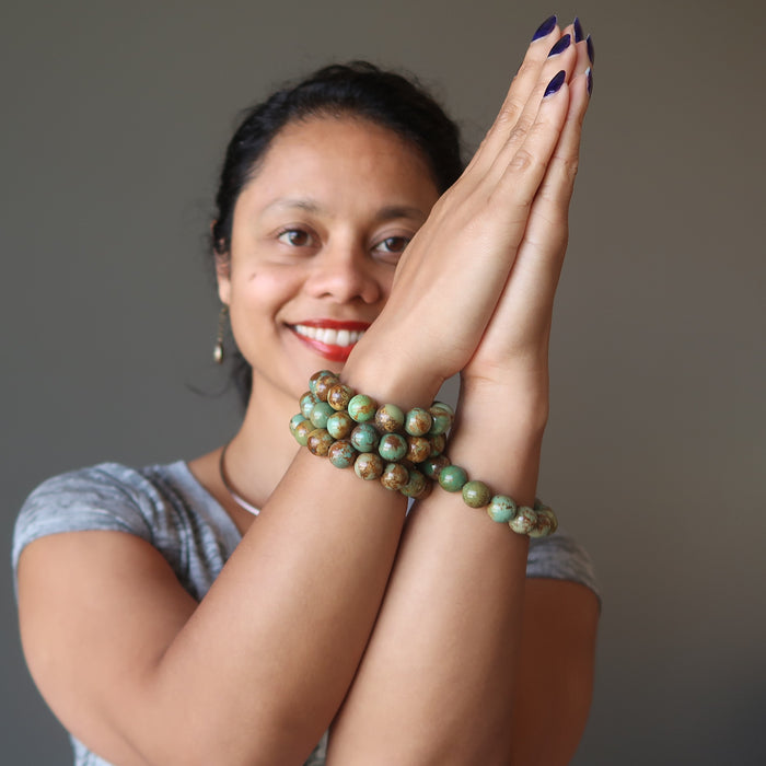 sheila of satin crystals with hands in prayer wearing green and brown turquoise jasper round beaded stretch bracelets