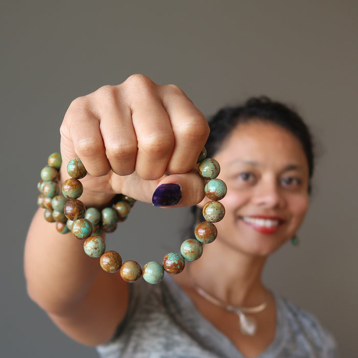 sheila of satin crystals wearing and holding green and brown turquoise jasper round beaded stretch bracelets