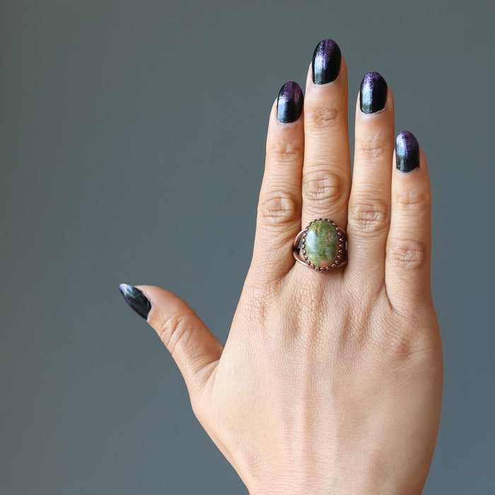 hand wearing unakite oval antique copper adjustable ring on middle finger