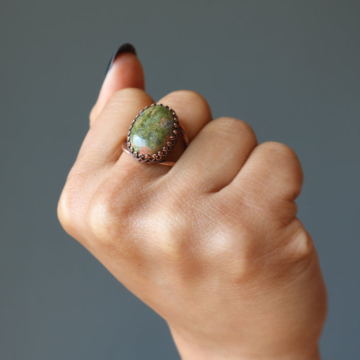 fist wearing unakite oval antique copper adjustable ring on middle finger