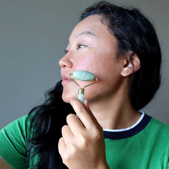 jessica of satin crystals using a jade roller on her cheek