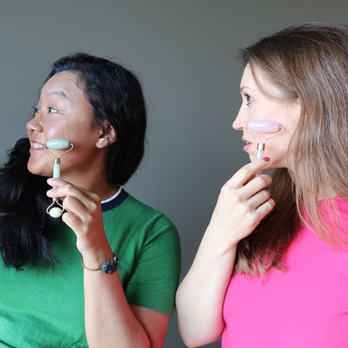 jessica of satin crystals using a jade roller on her cheek and holly using a rose quartz roller on hers