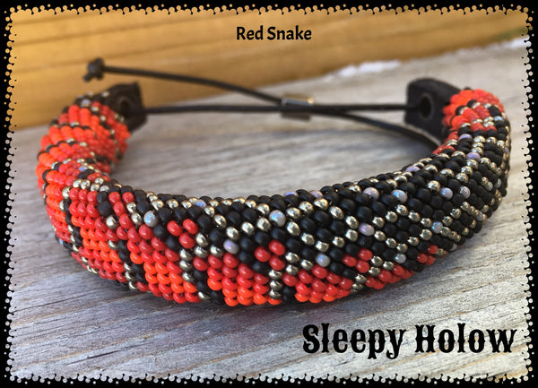 beaded design in shades of red, black and sliver in a snake skin design that twists around the bracelet, leather slide closure with a silver bead