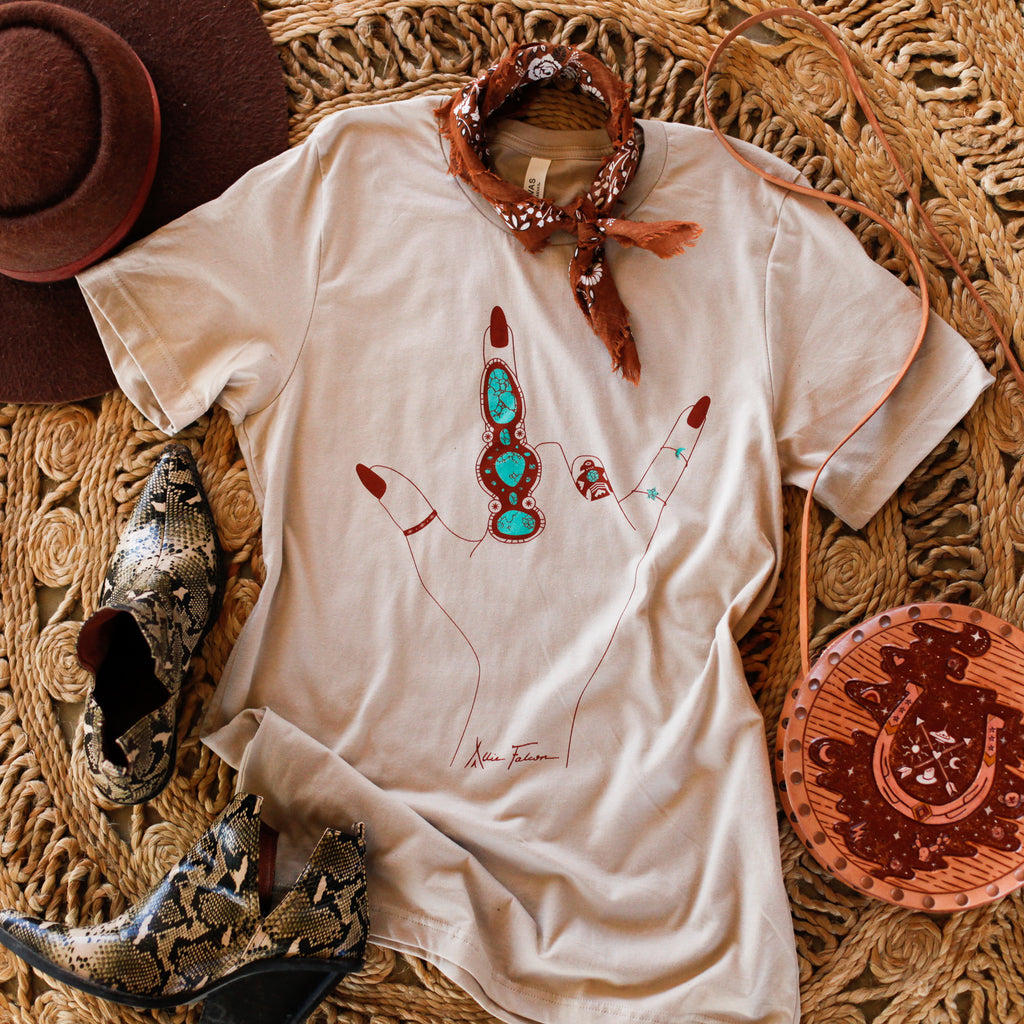 southwestern graphic tee with turquoise rings on it