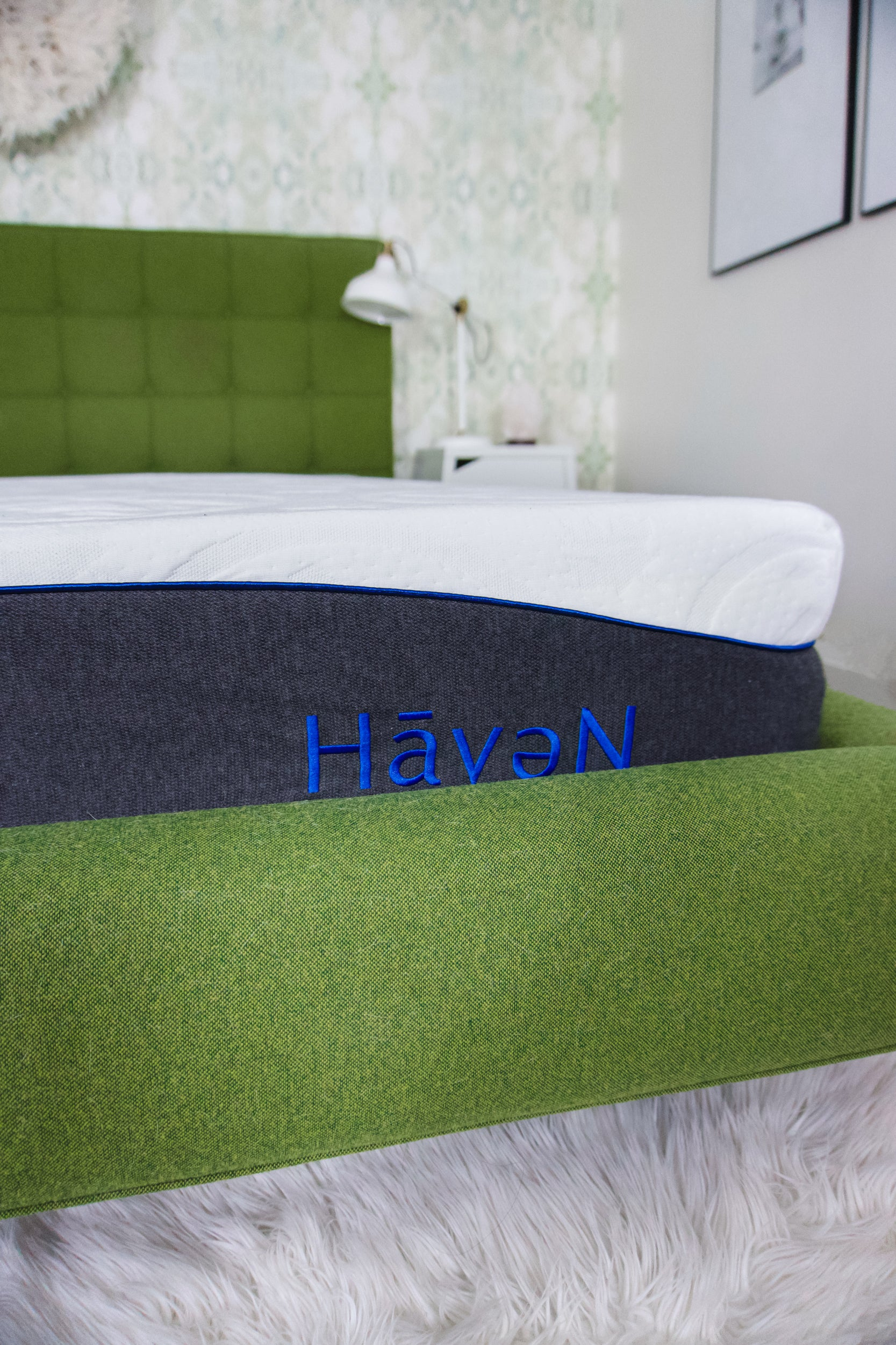 A Haven Mattress nestled in a soft green fabric-covered frame. Other design elements in the background.