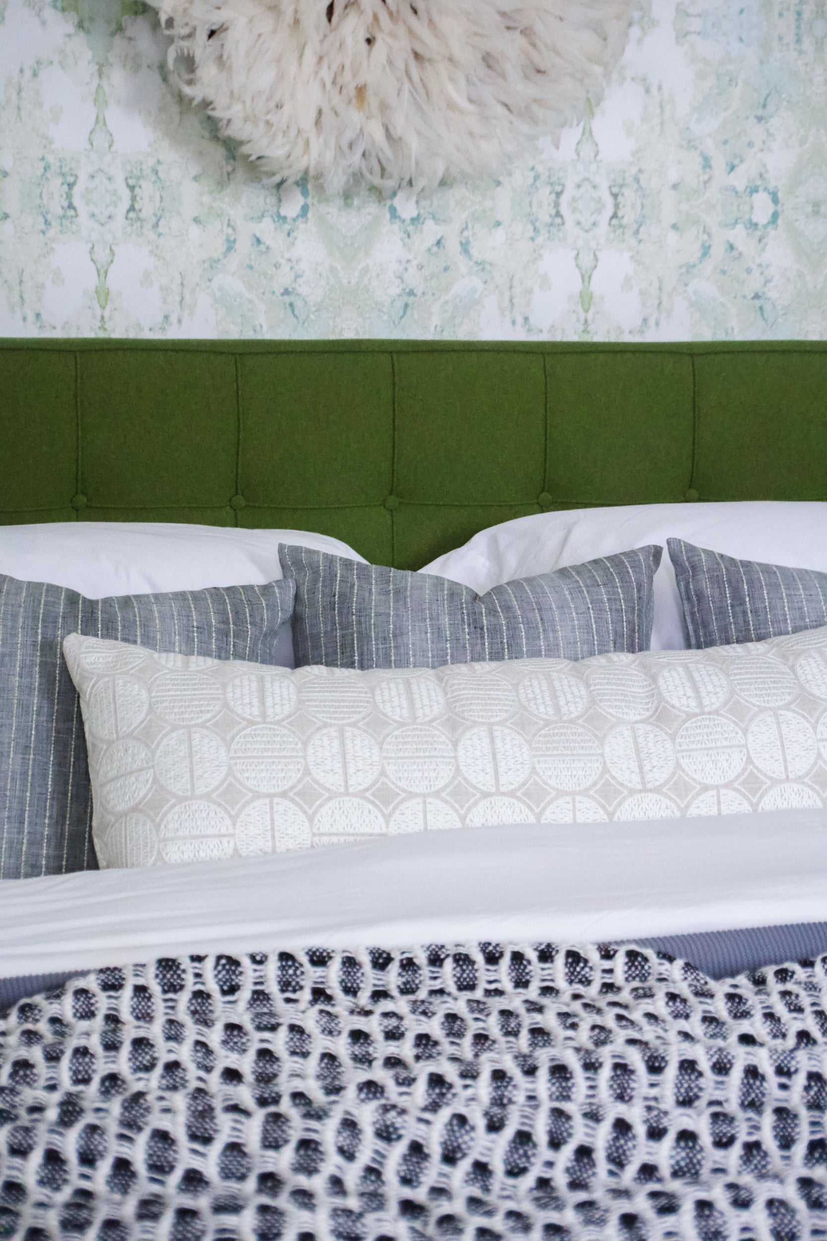 Cushions and pillows covered in textured bedding that is navy, white, grey and green