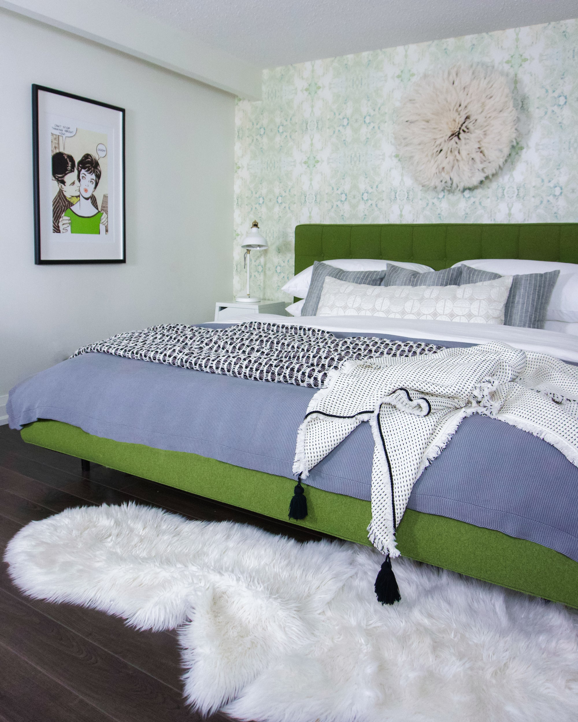 A master bedroom with a shaggy white rug and a pop art frame on the wall